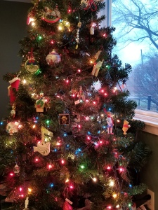 Tree in front of a large window with multicolored lights and ornaments.
